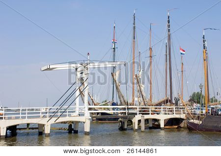 The old harbor in Volendam, the Netherlands, with a drawbridge, and old commercial sailing ships moored in the harbor