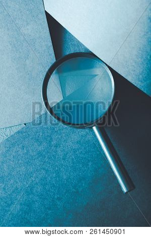 Magnifying Glass. Science Research Exploration And Scrutiny Concept. Loupe On Layered Blue Paper Bac