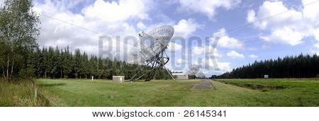 A neatly aligned row of radio telescopes, continuously scanning the universe near the second world war monument of Westerbork, the Netherlands