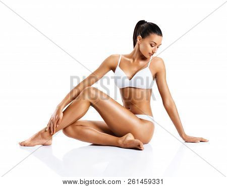 Beautiful Girl Touching Her Healthy Skin. Photo Of Young Girl Sitting On White Background. Beauty An