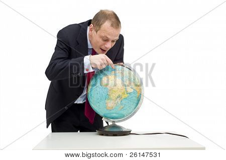A businessman discovering the potential of global business, visualized by his expression and pointing finger on the globe on the table in front of him.