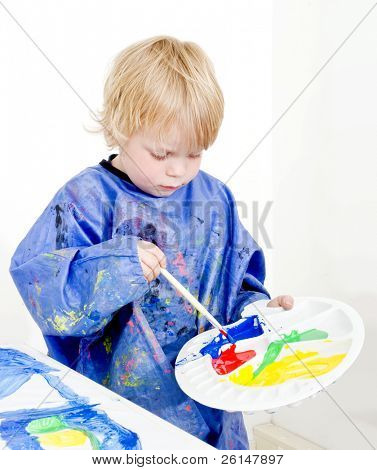 A young boy with a palette in his hand mixing poster paint with a brush