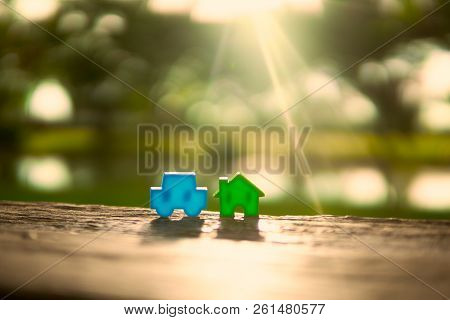 Blue House Model Green Car Model Is Located On Wooden Table. The Background Is The Sunlight To The M