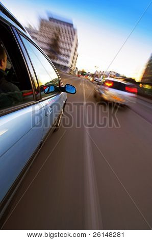A car passing another vehicle in an urban environment, seen from the outside of the car