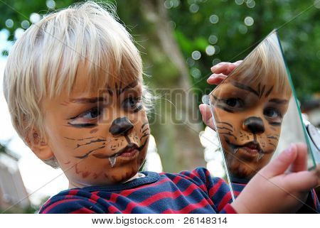 Young boy admiring his painted face in a small mirror