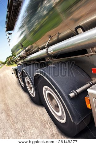 Cropped, motion-blurred, tilted close-up of semi on the road. No people are viewable in the shot. Vertically framed shot. poster
