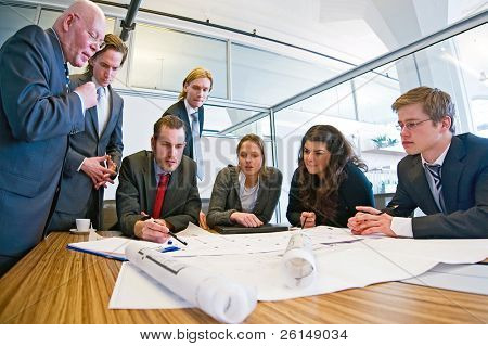 Group of seven designers discussing blueprints in a conference room.
