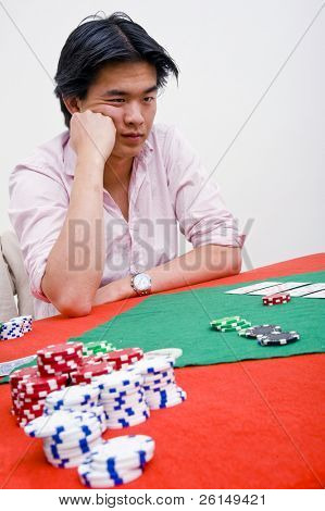 Asian poker player deciding whether to call or bluff