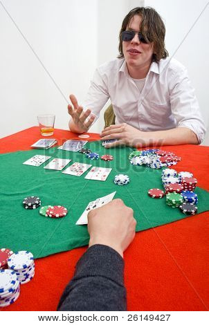 A poker player wearing large sunglasses calling his opponents bluff