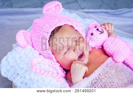 Cute Adorable Sweet Sleepy Newborn Infant Girl In A Pink Funny Cap With Ears Yawning. Strong And Ser