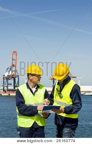 Two dockers discussing procedures and plans at the waters edge