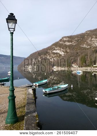 Lake With Two Boats On The Pier And A Lamppost In The Foreground