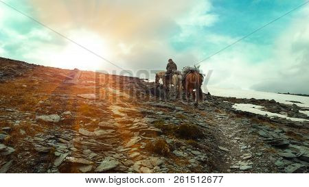 A Rider With Two Horses Walks Along The Path To The Mountains. Bags With Provisions On Horses. The R