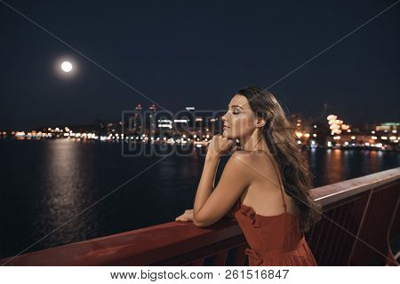 Young Ellegant Woman Standing On The Ligths Of The Night City Background On Bridge. Sexy Romantic Be