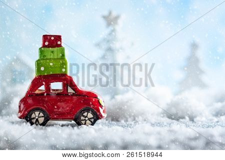 Red toy car carrying Christmas gifts in snowy landscape. Christmas concept with copy space.
