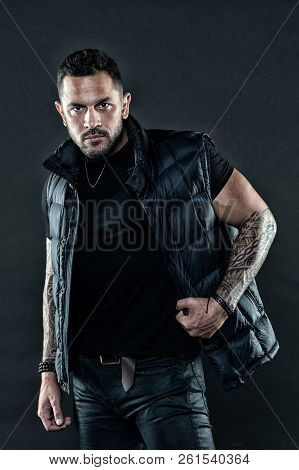 poster of Masculinity and fashion concept. Tattoo brutal attribute. Tattoo art concept. Macho unshaven brutal wear vest. Man brutal unshaven hispanic appearance tattooed arms. Bearded man posing with tattoos.