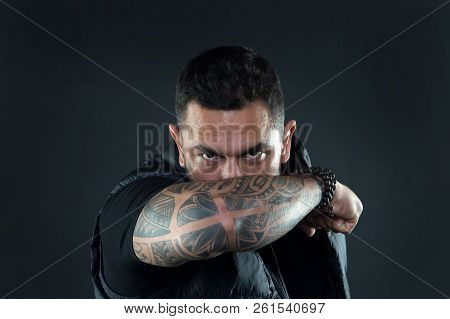 Do tattoos hide lack of masculinity. Man brutal guy cover face with tattooed arm. Tattooed elbow hide male face dark background. Visual culture concept. Tattoo can function as sign of commitment. poster