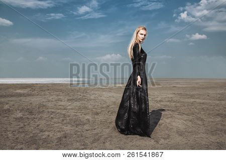 Full length portrait of a beautiful gothic woman in long black dress posing outdoor. Beauty, fashion.