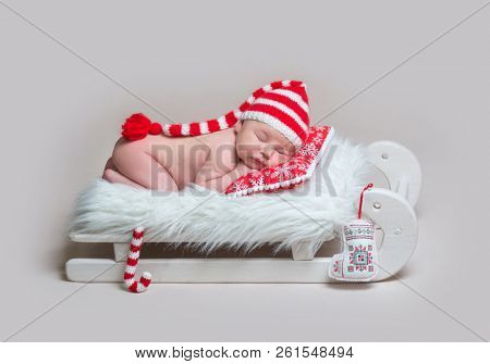 Charming infant baby in striped bonnet sleeping on red pillow on small wooden sledge crib with plush Christmas cane toy nerby