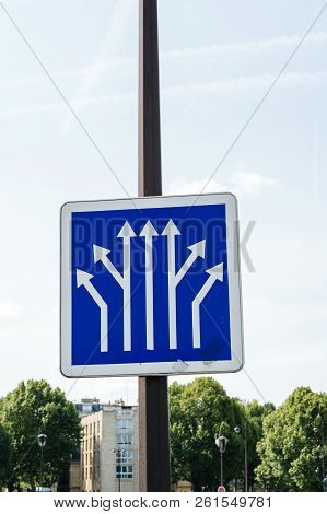 Blue Informational Traffic Sign Post Over A Clear Blue Sky Showing Multiple Branching Of Avenues In