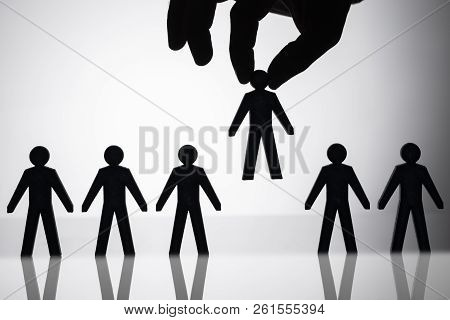 Person Picking Up Human Figure Amongst Others
