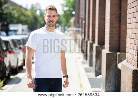 Portrait Of A Handsome Young Man Standing On Sidewalk