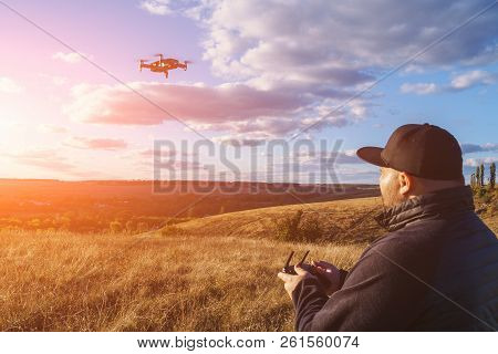 Man with remote controller operating flying drone or quad copter - modern small aircraft for aerial video making, toned poster
