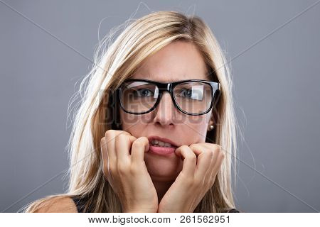 Nervous Woman Wearing Eyeglasses Biting Her Fingernail poster