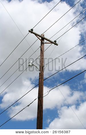 Telephone pole against cloudy sky poster