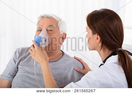 Doctor Holding Oxygen Mask Over Man's Face