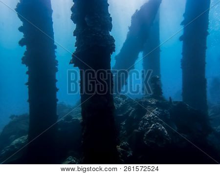 Coral Crusted Pier Pilings From Collapsed Pier In Silhouette Against Blue Ocean