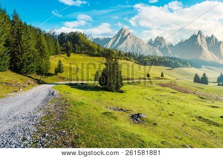 Country Road Winds Through The Valley. Mountains With High Rocky Peaks In The Distance. Composite Im