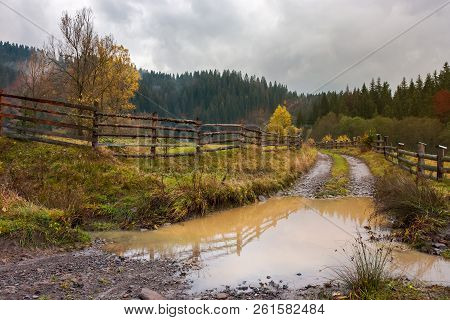 Huge Puddle On The Country Road. Wooden Fence Along The Path. Deep Autumn In Mountainous Countryside