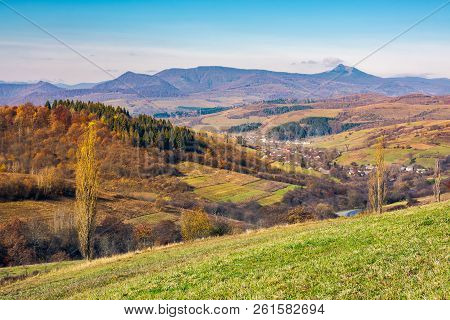 Lovely Countryside In Autumn. Village In The Nearest Mountain And Mountain Ridge With High Peak In T