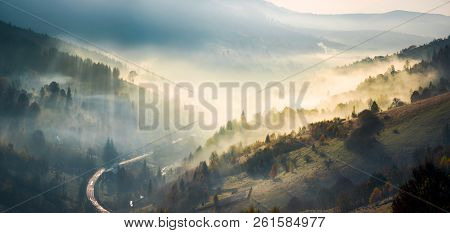 Panorama Of Amazing Scenery In Mountains At Sunrise. Glowing Fog Rise From Forest On Hills And Fall