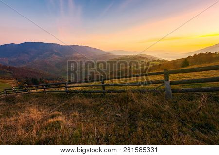 Beautiful Sunrise In Mountains. Wonderful Countryside Scenery In Autumn. Fence Along The Rural Field