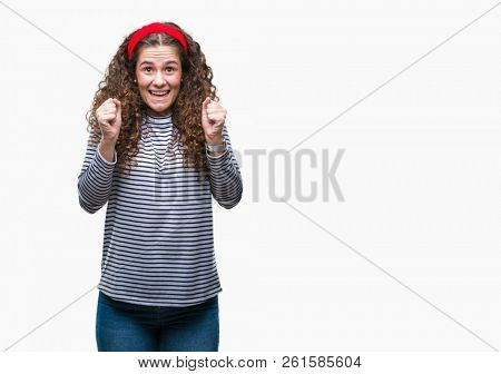 Beautiful brunette curly hair young girl wearing stripes sweater over isolated background excited for success with arms raised celebrating victory smiling. Winner concept.