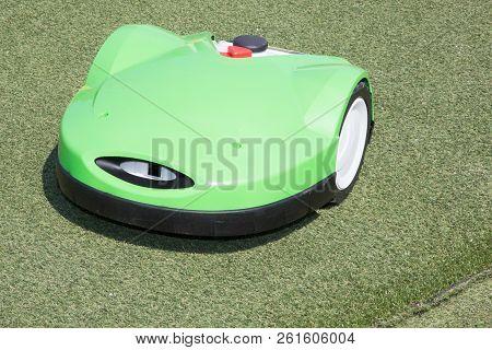 Robotic Lawn Mower Working On Green Grass Field