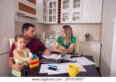 Family Budget And Finances- Young Couple With Daughter Planning Home Budget