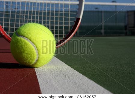 Tennis Ball on the court with racket in the background
