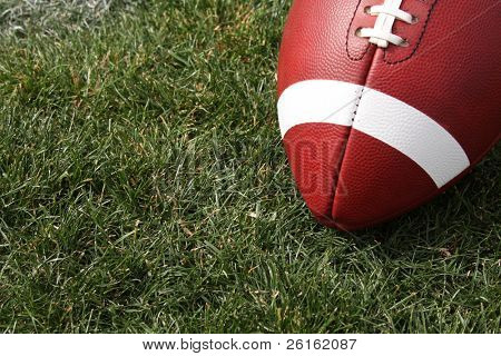 American Football close up on the grass with room for copy