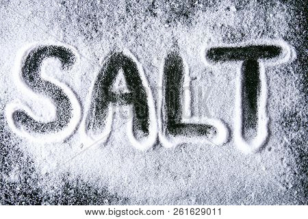 The Word Salt Is Written On Small Crystals Of Salt Scattered On A Black Table.