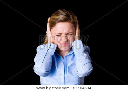 young attractive female in blue shirt covers her ears from noise, headache, pain and noise concept, studio shoot isolated on black
