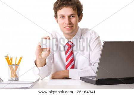 young businessman sits on his desk with laptop, pencils and paper tray and shows his empty, blank business card, studio shoot isolated on white