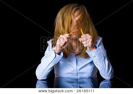 angry and stressed blonde businesswoman in blue shirt, studio shoot isolated on black background