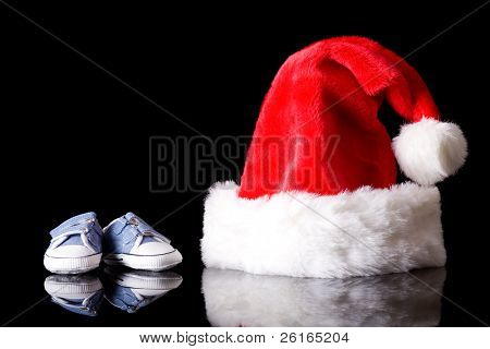 santa claus hat with pair of little baby shoes next to it, studio shoot isolated on black with reflection,