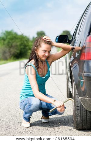 helpless young woman try to change wheel in her car