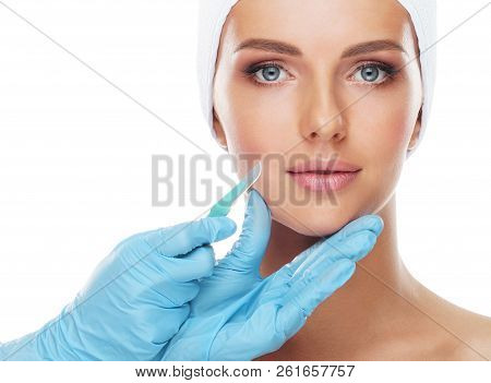 Beautiful Face Of The Young Woman And The Medical Scalpel In Doctor's Hands Isolated On White. Plast