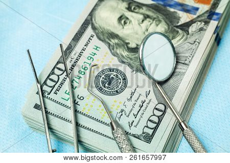Dental Tools Mirror, Tweezers And A Hook On A Stack Of Cash Dollar Bills. Concept Expensive Dentistr