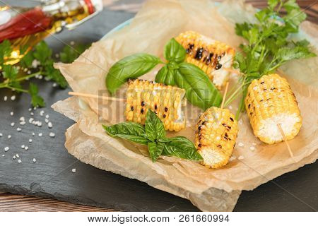 Corn Baked In Olive Oil, With Salt And Basil On Parchment Paper On A Dark Surface